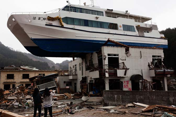 Nozomi Sabanai (L) together with her sister looks at catamaran sightseeing boat that was thrown by the tsunami onto a two story building, at Otsuchi town, Iwate prefecture on April 16, 2011.  Japan is considering issuing special bonds to fund reconstruction following last month's massive earthquake and tsunami, and imposing a new tax to repay the debt, a report said.