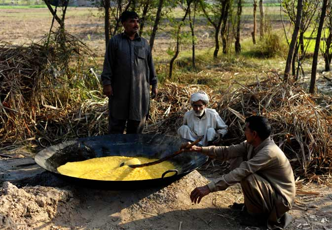 Pakistani farmers cook sugarcane juice in a field in Jalalpur Jattan, some 170 kilometres from Islamabad. Pakistan is Asia