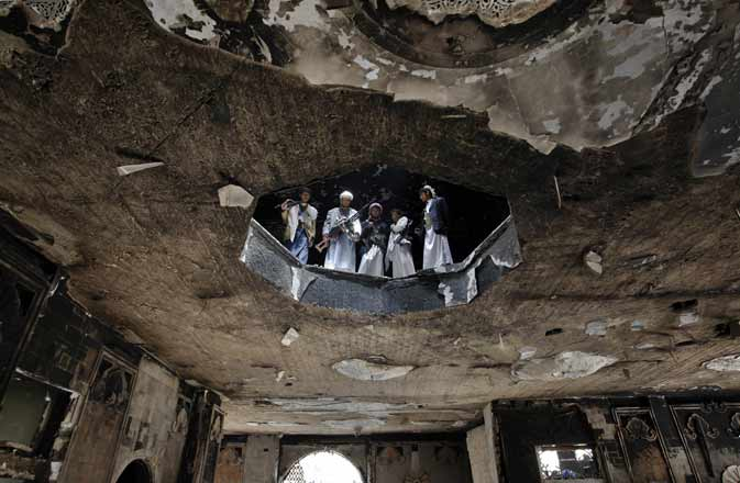 Armed Yemeni tribesmen loyal to dissident tribal leader Sheikh Sadiq al-Ahmar inspect damage at his house in Sanaa on June 7, 2011 while anti-government protesters demanded a swift transfer of power from Ali Abdullah Saleh as his deputy said the veteran Yemeni president would return within days after surgery in Riyadh for blast injuries.
