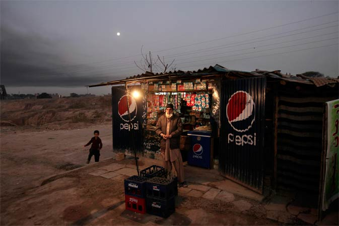 Pakistani Khan Badshah, 53, stands by his grocery store as he waits for customers on the outskirts of Islamabad, Pakistan. ? AP Photo