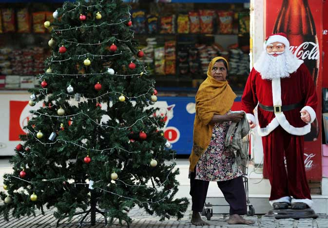 A Pakistani Christian woman walks beside a Santa Claus mannequin and Christmas tree displayed at a market in Islamabad on December 15, 2011. Christians in Pakistan and elsewhere in the world will celebrate Christmas.