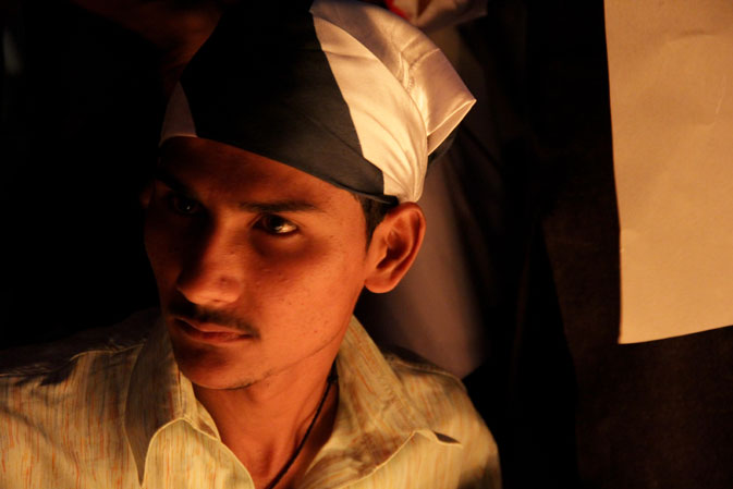 A representative of the ?Pakistan Awami Sangat? wearing the colours of the national flag round his head.