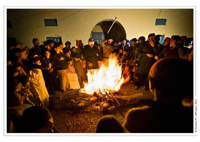 Pilgrims stand by the fire - Photo by Humayun Memon | 18% grey