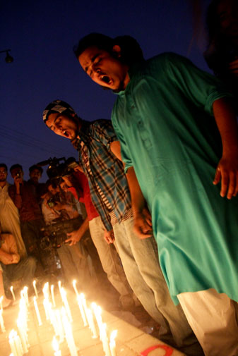 Passionate protestors sing the national anthem on the candle-lit sidewalk, amid cries of ?Go Nato Go!?