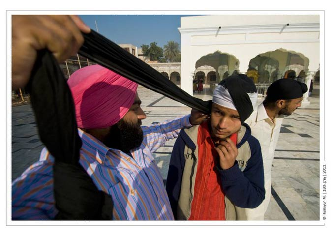 A pilgrim helps a young sikh put on his turban.- Photo by Humayun Memon | 18% grey