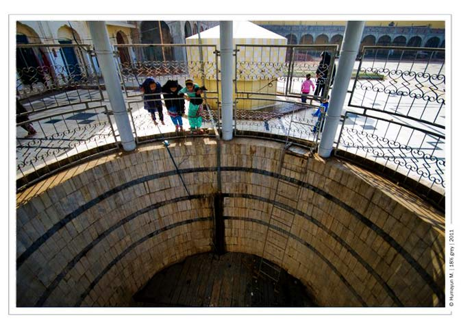 Children peek into a well located the compound of the Sikh temple- Photo by Humayun Memon | 18% grey
