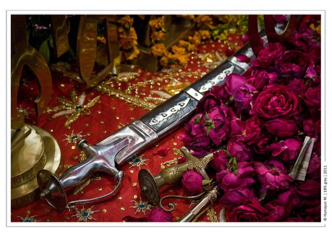 A sword placed on a table with roses at the Gurdwara- Photo by Humayun Memon | 18% grey