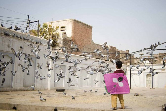 A kid feeding pigeons outside a shrine in Multan - Photo by Humayun M | 18% grey