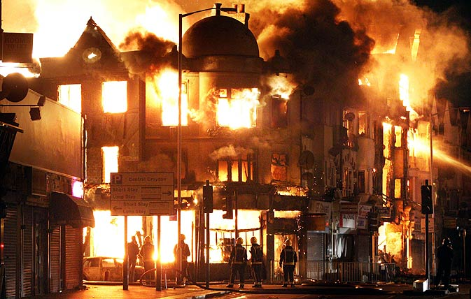 n this Aug. 9, 2011 photo, a property is on fire near Reeves Corner in Croydon, south London. A wave of violence and looting raged across London and spread to three other major British cities, as authorities struggled to contain the country
