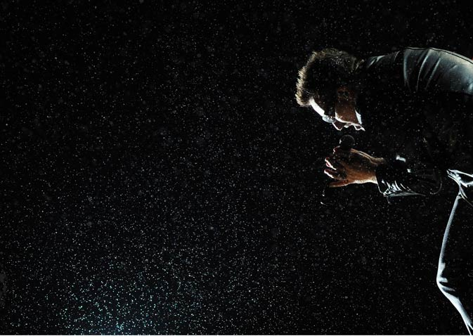 Bono of U2 performs in the rain on the Pyramid stage during the Glastonbury festival near Glastonbury, Somerset on June 24, 2011.