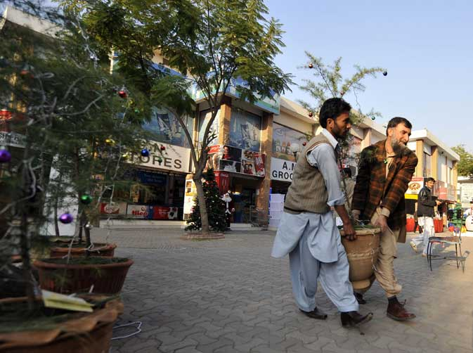 Pakistani men load an ornamental Christmas tree onto a vehicle at a market in Islamabad on December 15, 2011.