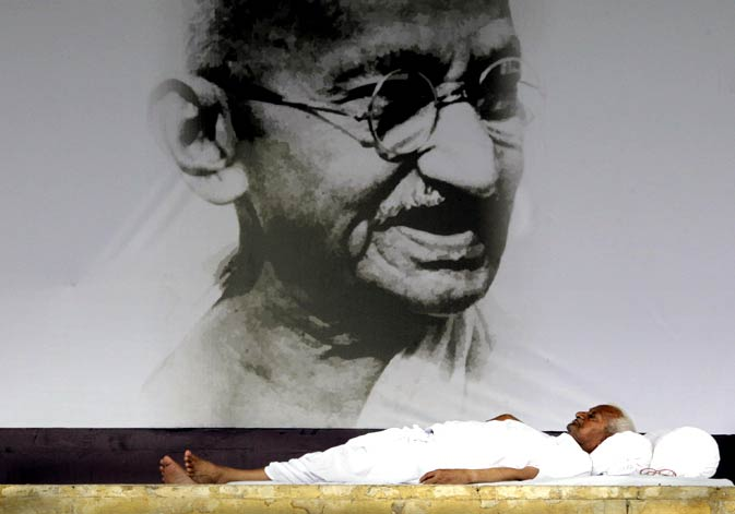 In this Aug. 24, 2011 photo, India's anti-corruption activist Anna Hazare rests in front of a giant portrait of Mahatma Gandhi on the ninth  day of his hunger strike, in  New Delhi, India.