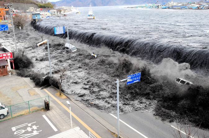 In this March 11, 2011 photo, a tsunami floods over the breakwater protecting the coastal city of Miyako at Heigawa estuary area after northeastern Japan was hit by a powerful earthquake.