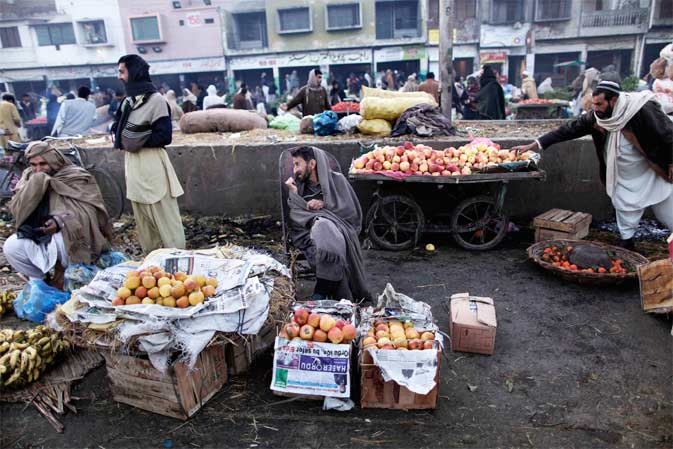Pakistani vendors sit next to their fruits waiting for customers at a wholesale market on the outskirts of Islamabad, Pakistan. ? AP Photo