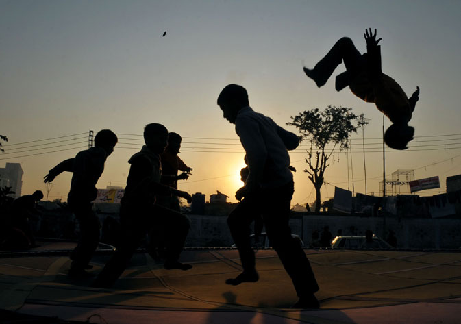 Pakistani minority Christian children play on a trampoline in Islamabad on December 17, 2011.