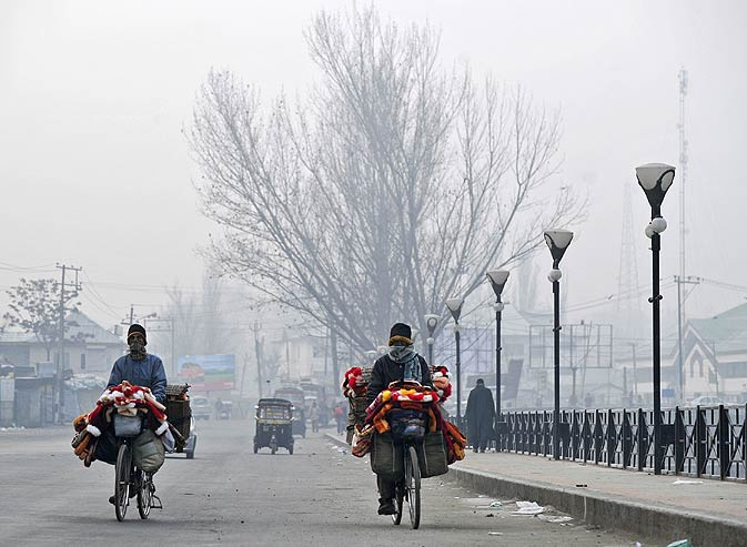 Kashmiri citizens ride bicycles  in Srinagar on December 27,2011. A cold wave further tightened its grip in Jammu and Kashmir with most places in the state recording sub-zero temperatures. -Photo by AFP