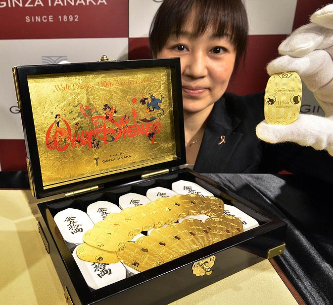 An employee of Tanaka Kikinzoku Jewelry displays a pure gold made oval coin designed with Mickey Mouse and Walt Disney on its surface for the celebration of the 110th anniversary of Walt Disney's birth at the company's main shop in Tokyo.  The 10gm oval coin is priced 85,500 yen (1,100 USD) while a set of 50 pieces in a wooden box is priced at 4.05 million yen (52,000 USD) and these coins will go on sale from January 2, 2012 for the New Year. -Photo by AFP