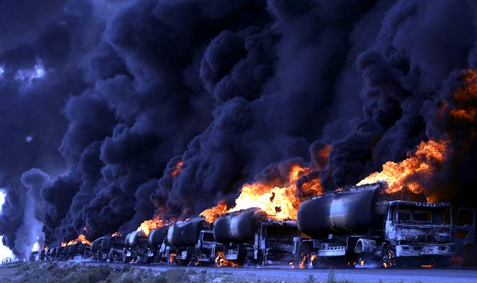 In this Aug. 22, 2011 photo, burning oil tankers carrying fuel for Nato forces in neighboring Afghanistan are seen along a road after being attacked by gunmen on the outskirts of Quetta, Pakistan.