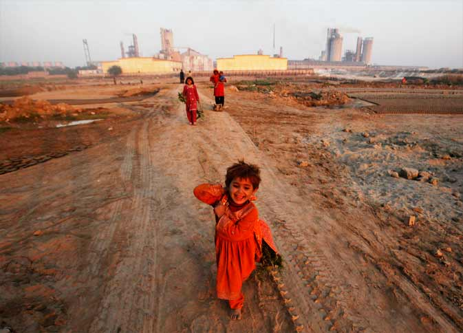 A young girl, whose family was making bricks, runs down a dirt road near the Pakarab (Pak-Arab) fertilizer factory in Multan December 14, 2011. U.S. lawmakers are ready to freeze up to $700 million in aid to Pakistan until Congress gets assurances that Islamabad is helping fight the spread of homemade bombs in the region, a move one Pakistani senator called unwise and likely to strain ties further. Many of the home made bombs are made using ammonium nitrate, a common fertilizer smuggled across the border from Pakis