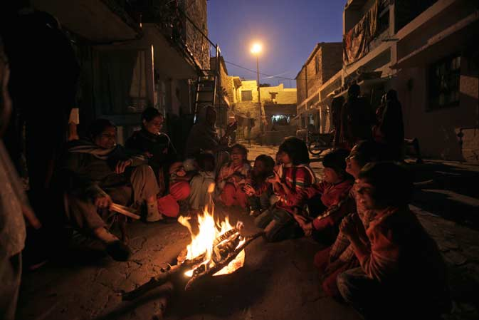 Pakistanis gather around a fire to warm themselves in an alley of a Christian neighborhood in Islamabad, Pakistan, Wednesday. ? AP Photo