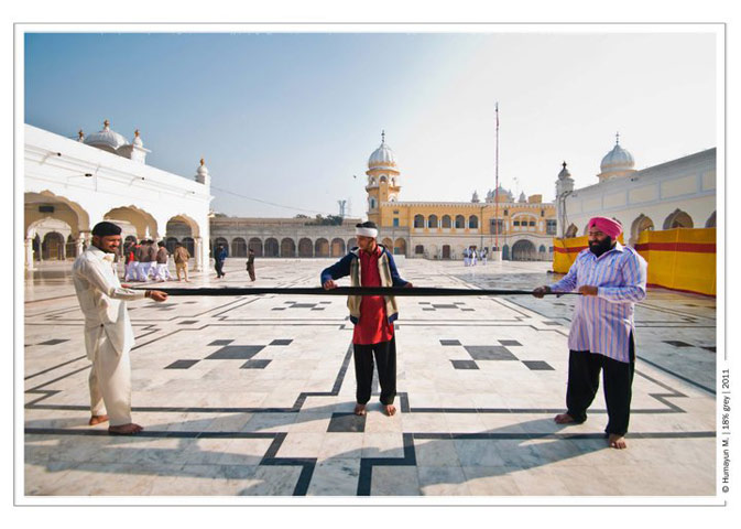 Three pilgrims stretch out a turban in order to fold it around their head- Photo by Humayun Memon | 18% grey