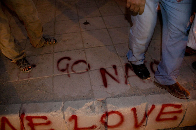 Some protestors have spray-painted their demands on the sidewalk as others walk on.