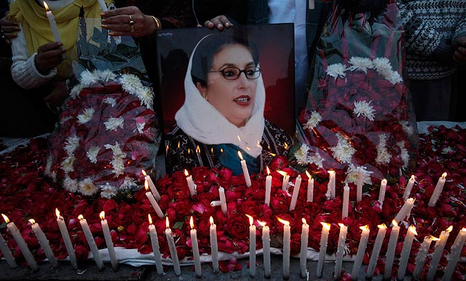 Supporters of Pakistan People's Party hold an image of Pakistan's former prime minister Benazir Bhutto during a candlelight vigil to commemorate her death anniversary in Lahore December 26, 2011.  Bhutto was killed in a gun and suicide bomb attack after an election rally in the city of Rawalpindi on December 27, 2007, weeks after she returned to Pakistan after years in self-imposed exile. -Photo by Reuters