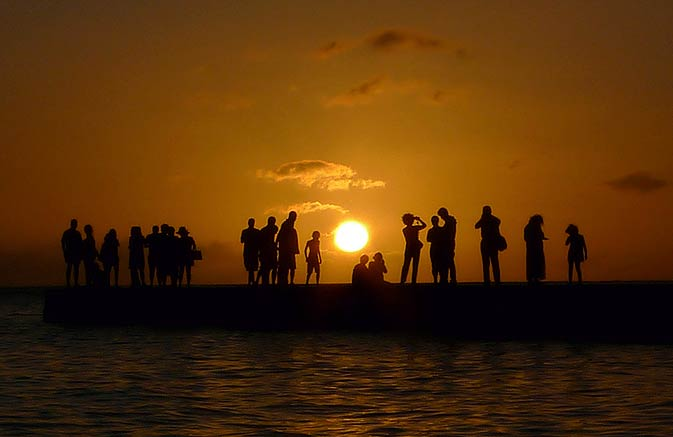 Tourists watch the sun setting over a point on Waikiki Beach in Honolulu. -Photo by Reuters