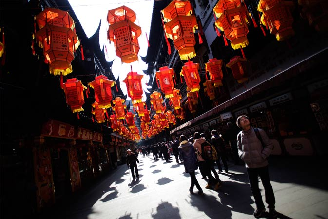 Tourists walk under the lanterns for Spring Festival displayed at the centuries-old Yuyuan Garden, one of the most popular tourist spots in town, ahead of spring festival celebrations next week in Shanghai, China on Tuesday January 17, 2012. - AP Photo