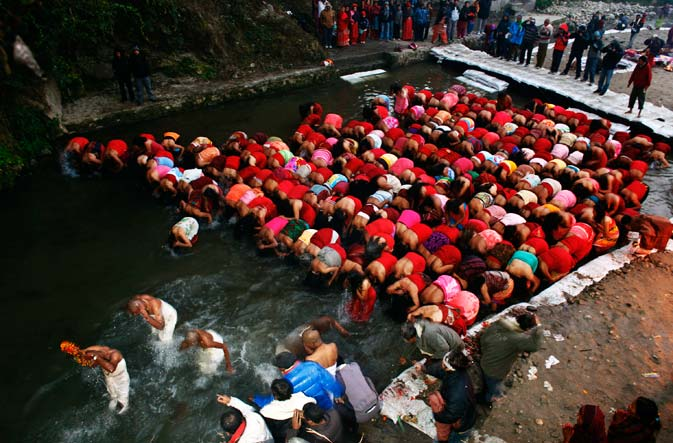 Nepalese Hindu women take holy dips at the Salinadi River during the first day of Madhav Narayan Festival. Hindu women observe a fast and pray to Goddess Swasthani for the longevity of their husbands during the festival. ? AP Photo