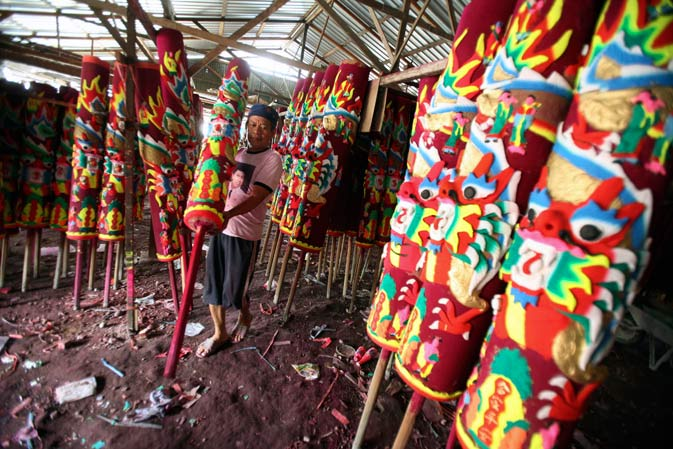 A worker arranges large joss sticks in preparation for Chinese New Year celebrations in Medan, North Sumatra, Indonesia. - AP Photo
