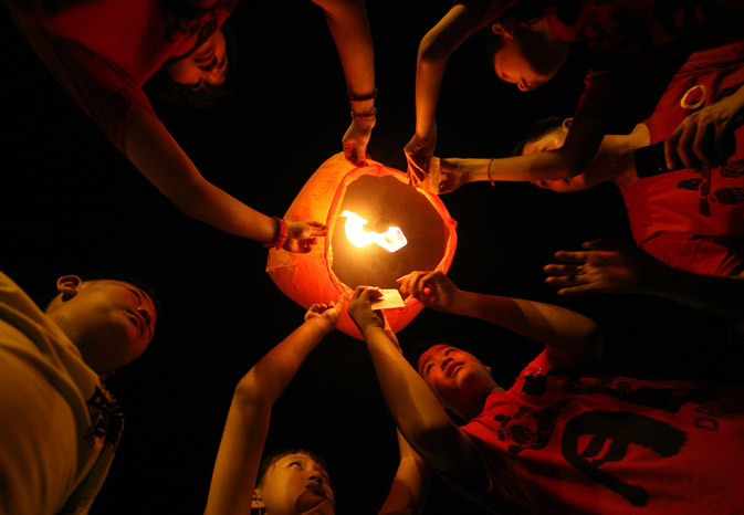 Indonesian ethnic Chinese hold a lantern together before releasing it to celebrate the Chinese Lunar New Year in Medan, North Sumatra, Indonesia. - AP Photo