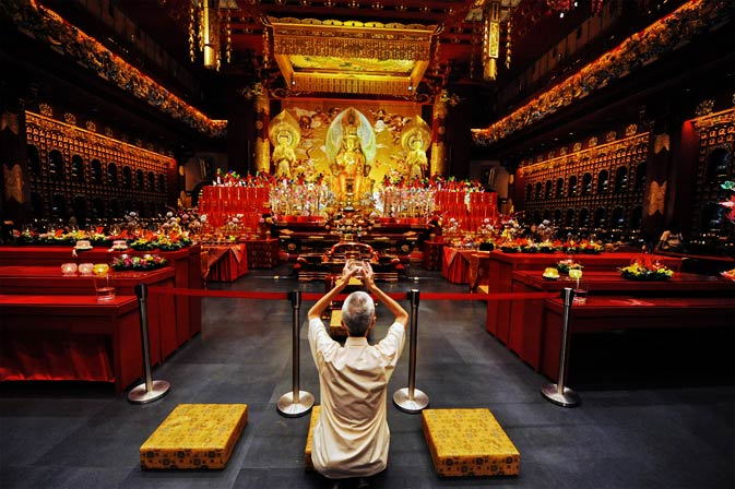 A man prays inside the Buddha Tooth Relic Temple and museum ahead of the Lunar New Year in Singapore on January 20, 2012. - AFP Photo