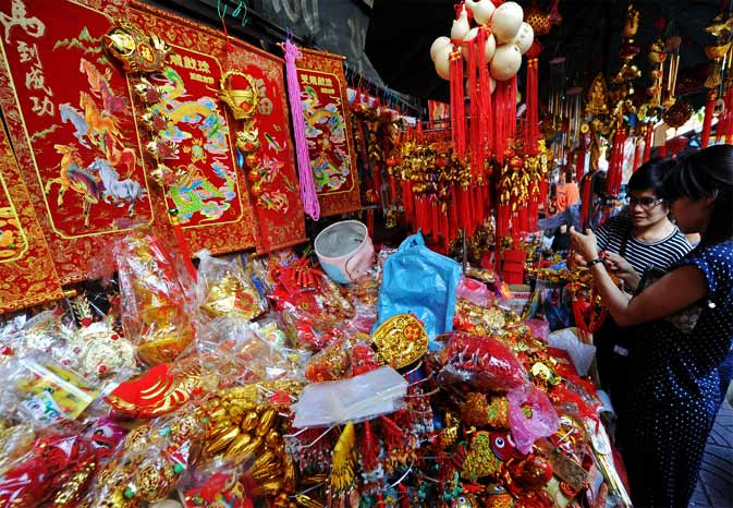 People inspect decorations ahead of the Lunar New Year at China town in Bangkok. - AFP Photo
