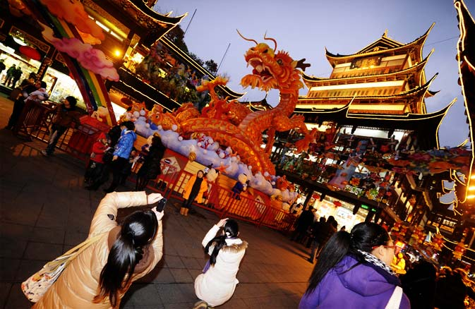 People look at decorations for the upcoming Chinese New Year of the Dragon in Shanghai on January 19, 2012. - AFP Photo