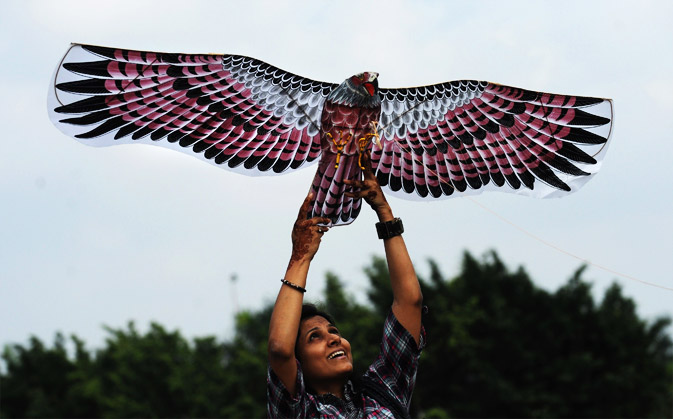An Indian woman holds a kite representing an eagle during a Kite Festival in Kolkata, on January 19, 2012. Kite enthusiasts, school children and others participated in the festival promoted jointly by the state govermnent and the Japan Foundation. - AFP Photo