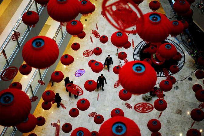 Customers walk through the hall of a local shopping mall beneath red lanterns put up as Spring Festival decorations in Nanjing, Jiangsu province. - Reuters Photo
