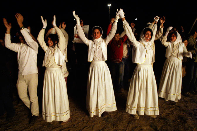 Joyful Iranian Zoroastrian young people join hands and clap, as they celebrate their ancient mid-winter Sadeh festival, outside the capital Tehran, Iran, Monday, January 30, 2012, after setting a giant bonfire.