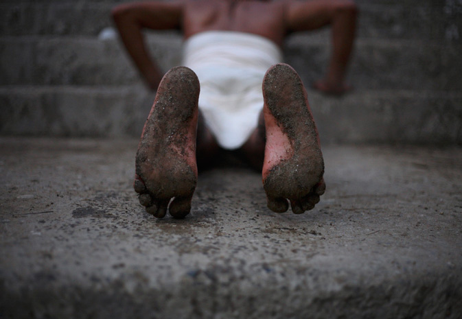 A Hindu devotee's feet are seen while he rolls on the ground during the first day of Swasthani Brata Katha festival at Saali River. - Reuters Photo