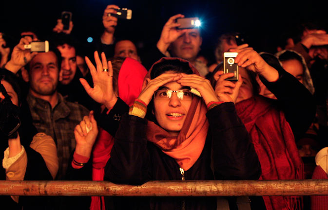 Iranian Zoroastrians look at and take pictures of a giant bonfire, set alight for their ancient mid-winter Sadeh festival.