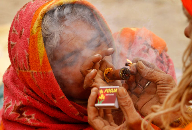 """A Hindu women smokes marijuana as she sits at the Sangam on """"Paush Purnima,"""" the first auspicious day of holy dip during Magh Mela at Sangam in Allahabad, India. Magh Mela, the annual Hindu ritual, involves bathing on auspicious dates spread over a period of 45 days. ? AP Photo"""