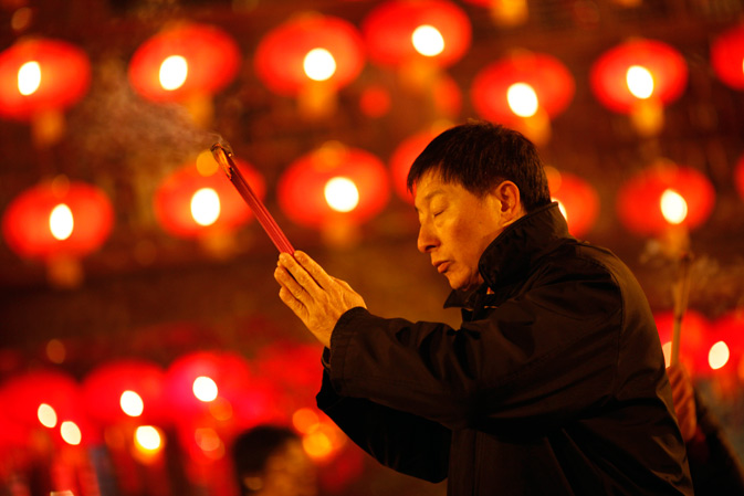A man holds incense sticks as part of Chinese new year celebrations at the Old City God Temple in Yuyuan Garden in Shanghai January 22, 2012. - Reuters Photo