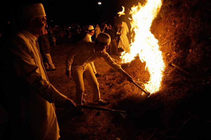 An Iranian Zoroastrian priest, left, and youths sets fire to an already prepared pile of wood, as they celebrate their ancient mid-winter Sadeh festival, outside the capital Tehran, Iran, Monday, January 30, 2012.