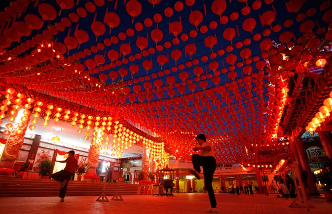 Malaysians of ethnic Chinese descent perform tai chi exercises underneath lanterns at Thean Hou Temple in Kuala Lumpur. - Reuters Photo