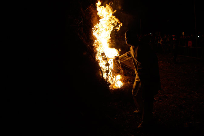 An unidentified Iranian Zoroastrian priest, sets fire to an already prepared pile of wood, during celebration of Zoroastrians ancient mid-winter Sadeh festival, outside the capital Tehran, Iran, Monday, January 30, 2012.