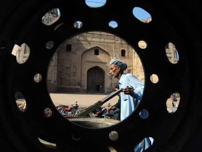 This photograph taken on November 16, 2011 shows a labourer pushing his cart beside the Lahore Fort in the walled city of Lahore.