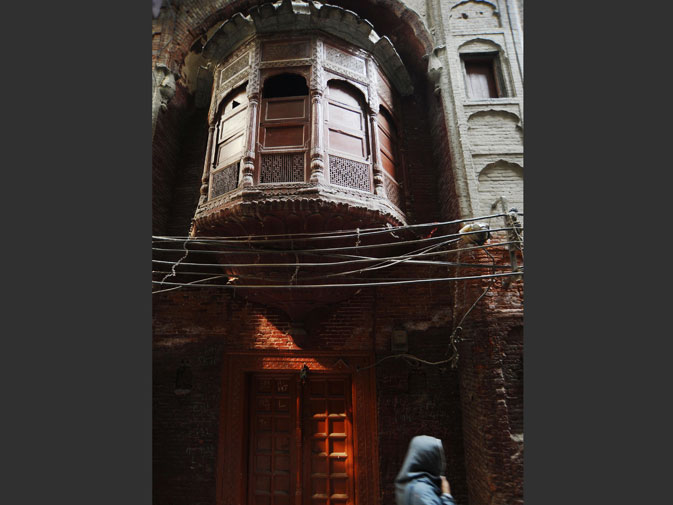 This photograph taken on October 29, 2011 shows a woman walking past an old residential area of the walled city in Lahore.