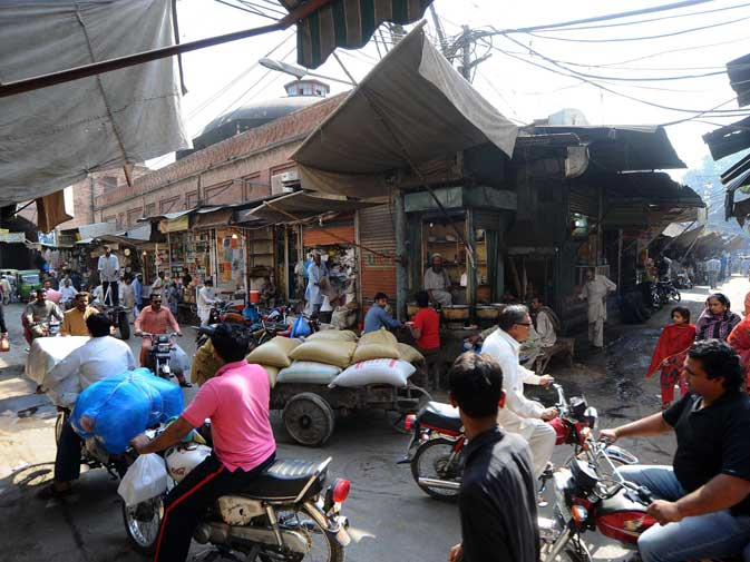 This photograph taken on October 29, 2011 shows commuters and pedestrians on a street in the old walled city of Lahore.