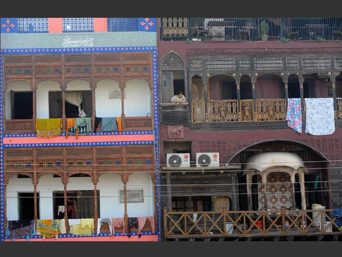 This photograph taken on October 29, 2011 shows a Pakistani woman (C-top) looking out from a balcony in the old residential walled city of Lahore.