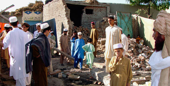 Tribesmen gather it a house was hit by a suspected US missile in Mir Ali village near Miran Shah, the main town of North Waziristan tribal region on November 1, 2008. — File photo by AP